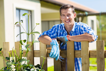 young man leaning on fence relaxing
