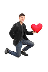 Man crouching on one knee and holding a red heart