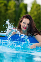 Woman in the garden splashing water from pool
