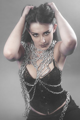 Beautiful brunette woman with big silver chains chained