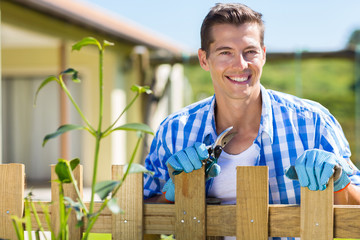 young man standing by home garden fence