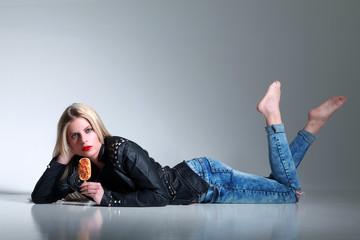 Junge blonde Frau mit Spaghetti Eis am Stil liegt am Boden