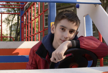 the teen boy is driving car on the playground