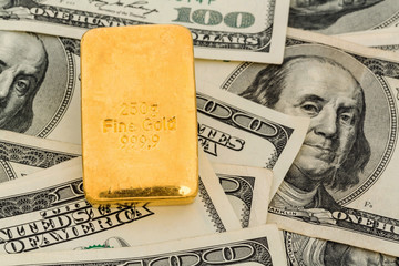 gold bars on dollar bills