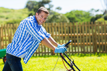 young man pushing lawnmower