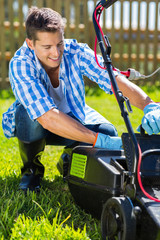 young man emptying lawnmower grass catcher