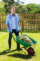 young man pushing wheelbarrow full of grass