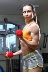 девушка выполняет упражнение с гантелями