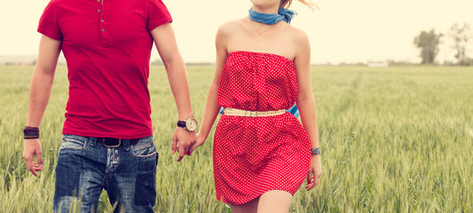Holding hands couple on green field