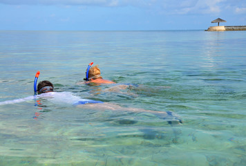 Man and woman snorkling in the sea - Maldives