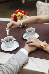 Coffee cups and holding hands and putting suger in coffe