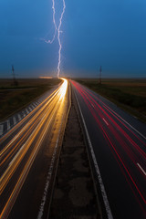 Thunderstorm and lightnings in night over highway with cars movi