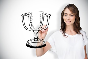 Composite image of businesswoman drawing winners cup