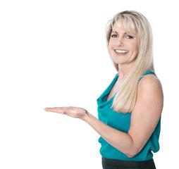 Lachende Blondine präsentiert ein Produkt: Handfläche