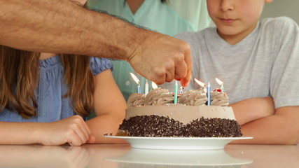 Father lighting candles on birthday cake for his family