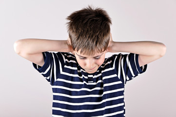 Young boy bending his head and covering ears with hands