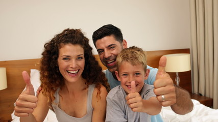 Parents and son sitting on bed giving thumbs up to camera