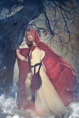 Young woman in red cape standing under winter season tree
