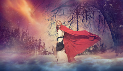 Young woman in red cape under magical winter tree