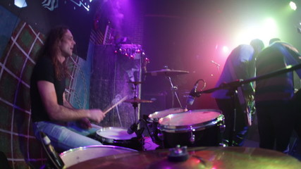 Musician playing drums on stage, rock music concert