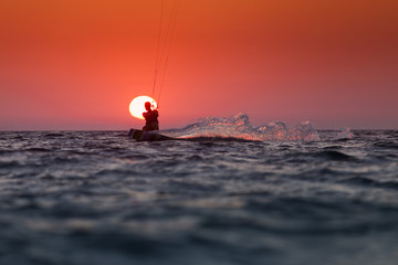 Silhouette of a kitesurfer sailing at sunset over the sun
