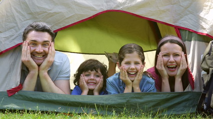 Funny family on a camping trip in their tent