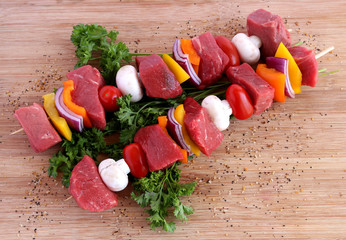 Uncooked beef kebabs with vegetables and spices