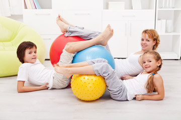 Happy healthy family with large gymnastic balls