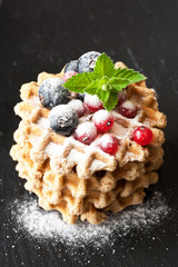 Waffles with berries currants. Chalk board background