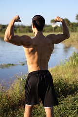 male bodybuilder model back view. outdoors