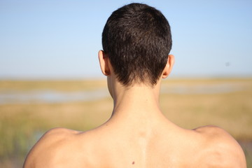 Back of young man in yoga position. outdoors