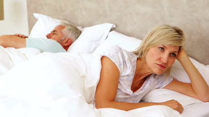 Couple not speaking to each other in bed