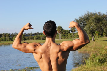 Fit male model showing his biceps and back