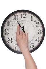 Weibliche Finger ändert die Zeit auf einer Uhr