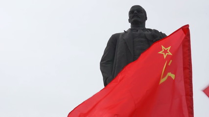Monument to Vladimir Lenin end soviet flag flying.