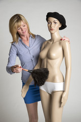Woman dusting a manikin model from the shop window