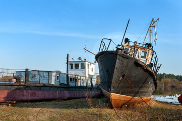 broken rusty ships standing on the river bank