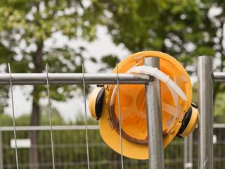 Ein gelber Schutzhelm mit Gehörschutz hängt an einem Bauzaun