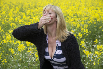 Woman covering her nose and mouth in a rapeseed field