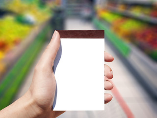 white blank notebook in woman hand and supermarket background