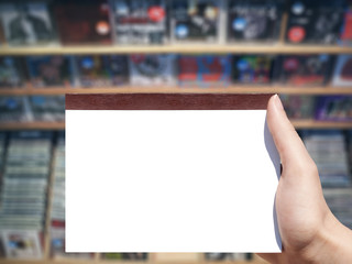 white blank  notebook in woman hand and music store background