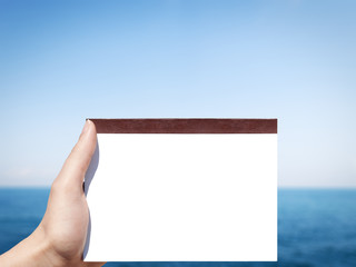 horizontal white blank notebook in woman hand and sea background