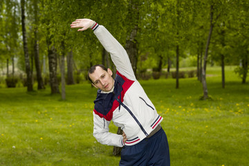 Attractive vigorous man plays sports in park