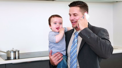 Father holding his baby son before work and talking on phone