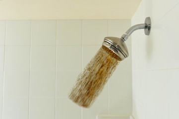 Shower head with dirt pouring out of it