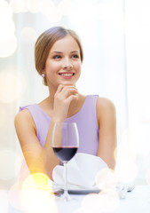 smiling woman with glass of whine waiting for date