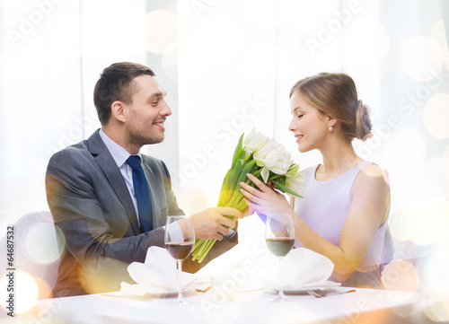 smiling man giving flower bouquet at restaurant