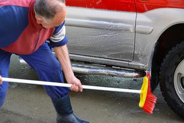 hombre mayor limpiando un coche rojo con un cepillo