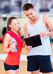 smiling male trainer with woman in the gym