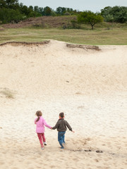 children running into a dune landscape